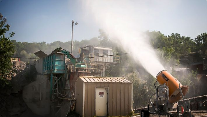 Dust control cannon at mining facility using atomized mist