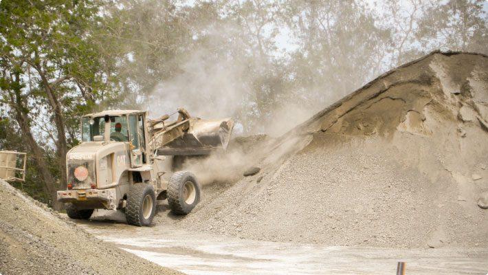 excavator dumping bucket at limestone crushing facility