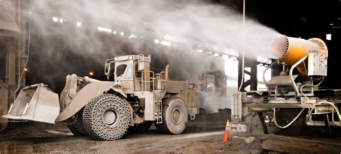 Dust control system throwing mist at steel mill roadway