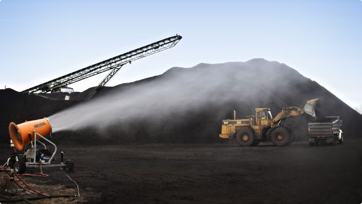 Dust cannon throwing atomized mist at coal stockpiles with machinery unloading