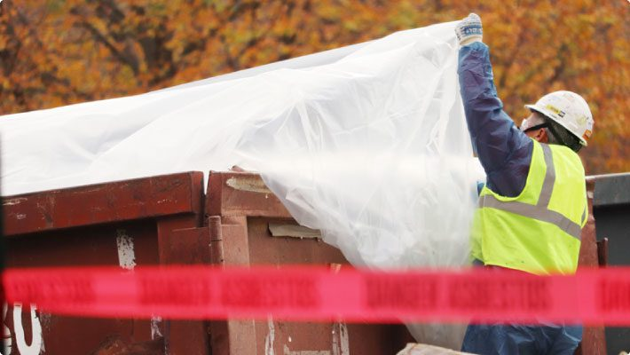 Worker avoid effects of fugitive dust at waste container